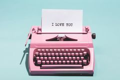 Pink vintage typewriter with a white sheet of paper. And `I love you` written on it. Love concept Stock Image