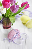 Tulips and easter eggs. Pink, violet and white tulips in a glass vase with easter eggs on wooden background royalty free stock images