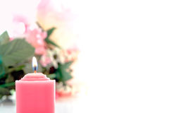 Pink Votive Candle and Pastel Flower Bouquet. Pink votive candle burning with a soft glow before a pastel color flower bouquet in background over white stock images