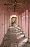 Pink walkway. A man walks under a arched walkway in St. Croix Stock Photography
