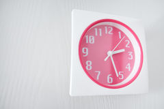 Pink wall clock looking from side view Stock Images