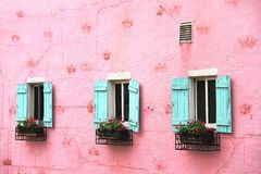Pink wall of a house with blues windows in La Provence Village. Colorful sights in  French style, South Korea Stock Photos