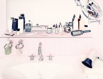 Pink wall and a shelf in the bathroom with hygiene accessories. Royalty Free Stock Images