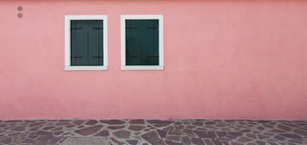 Pink wall and two window. In Burano, Venice Royalty Free Stock Photography