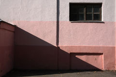 Pink wall with window and shadow. Stock Photo