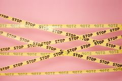Pink wall with the yellow scotch tapes with inscriptions of word `stop` on it stock image