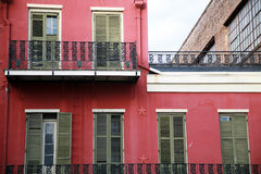Pink Walls Green Shutters. A building in the French Quarter of New Orleans with pink walls, green shutters and Mardi Gras beads hanging on the rails Royalty Free Stock Photography