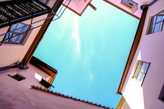 Pink walls and a piece of blue skies above. Taken from below stock illustration