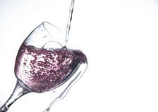 Pink water being poured into a wine glass Royalty Free Stock Images