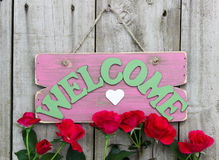Pink weathered welcome sign with heart hanging on door with flower border of red roses Stock Photo