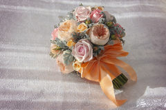 Pink wedding bouquet with orange bow. On a silk sheet Stock Photo