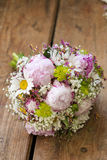 Pink wedding bouquet. Round, pink wedding bouquet of peonies and daisyes Royalty Free Stock Image