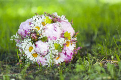 Pink wedding bouquet. Round, pink wedding bouquet of peonies and daisyes Royalty Free Stock Images