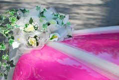 Pink wedding car bonnet with bouquet of flowers. Pink, classic-styled wedding car with a bouquet of flowers attached to the front of the bonnet Royalty Free Stock Photos