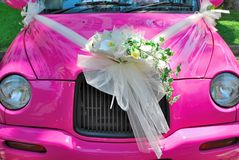 Pink wedding car with bouquet of flowers Stock Images