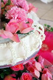 Pink Wedding Flowers and Cake. Wedding cake with pink flowers and white decorative icing Royalty Free Stock Image
