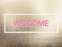 Pink welcome word in white frame on dramatic rough polish black leather stock image