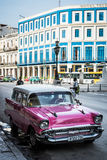 Pink white american classic car parked before a building in Havana city Royalty Free Stock Image