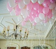 Pink and white balloons floating in the room royalty free stock photography
