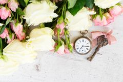 Pink and white blooming roses. With sceleton key and antique clock stock photos