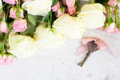 Pink and white blooming roses. With sceleton key, copy space on wooden table royalty free stock photo