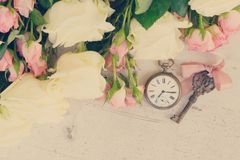 Pink and white blooming roses. With sceleton key and antique clock, retro toned stock images