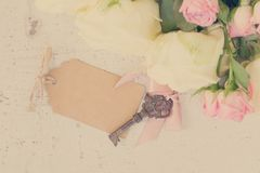 Pink and white blooming roses. With sceleton key, copy space on paper note, retro toned royalty free stock image