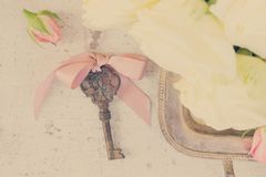 Pink and white blooming roses. With sceleton key, retro toned stock photo