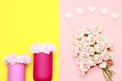 Pink white bouquet of roses, heart shaped stones and flowers on the jars with yellow background, mothers day celebration. Pink and white bouquet of roses, the Stock Image