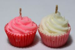 Pink and white candles in cupcake shape put on light grey background. stock image