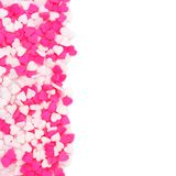 Pink and white candy heart sprinkles border over white Royalty Free Stock Images