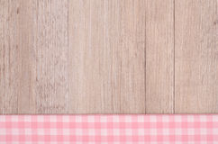 Pink and white checkered cloth. On wood as background stock photo