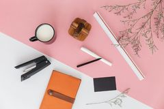 Pink and white color background with flower branches, scale ruler, a cup of milk, pen, pencil, stapler, sketchbook. Pink and white color background with flower royalty free stock photography