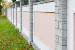 Pink and white concrete fence with stone columns Royalty Free Stock Photos