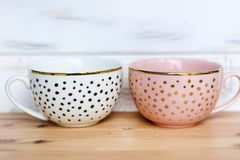 Pink and White Cups with Dots. Pink and white  cups with black and golden  decorative  dots Stock Photo