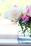 Pink and White Flowers. White roses and pink tulips in clear glass vase stock photos