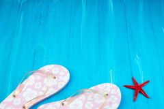 Pink with white flowers flip flop sandals beach shoes on blue wooden floor. Top view and copy space. royalty free stock photos