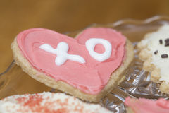 Pink and white frosted heart Valentine cookie with the letters X stock photography
