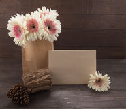 Pink and white gerbera flowers and pine cones are in the bag, on the wooden background with card. Stock Image