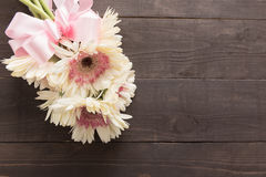 Pink and white gerbera flowers with ribbon are in the wooden background. Stock Photo