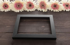Pink and white gerbera flowers are in the wooden background with picture frame. Stock Photo