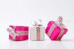 Pink and white gift boxes tied with white red stripe ribbon. Pink and white color gift boxes tied with white red stripe ribbon isolated on white background royalty free stock photo
