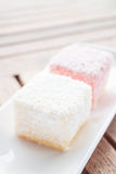 Pink and white lamington cakes on wood table Stock Photo