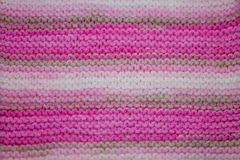 Pink, white and light brown striped knitted texture background. A pink, white and light brown striped knitted texture background stock image
