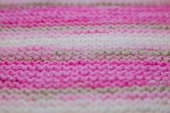 Pink, white and light brown striped knitted texture background. A pink, white and light brown striped knitted texture background stock photos