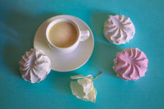 Pink and white marshmallows and cup with a cappuccino on a turquoise background Stock Photos