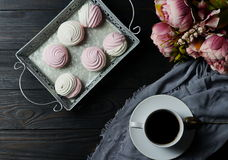 Pink and white marshmallows on a dark background on a vintage tray and bouquet of flowers. Pink and white marshmallows on a vintage tray, coffe and bouquet of royalty free stock photo