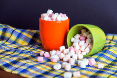 Pink and white marshmallows spilling from a green cup, over old wood background. Shallow depth of field Royalty Free Stock Photos