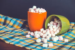 Pink and white marshmallows spilling from a green cup, over old wood background. Vintage effect with intentional vignette. Royalty Free Stock Photos