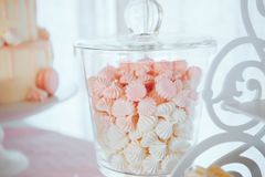 Pink and white meringues in glass jar. Gentle dessert royalty free stock photo
